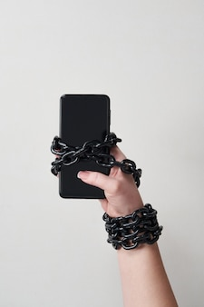 Iron chain that ties together hand and smartphone in concept of social media and internet addiction