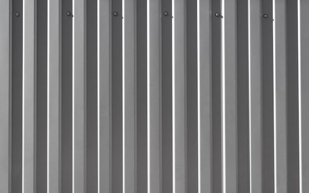 壁にねじ込まれた鉄構造の灰色のプロファイルシート。建築材料に面するか屋根を付ける。テクスチャード加工された不均一な鋼の背景、テキスト用のコピースペース。