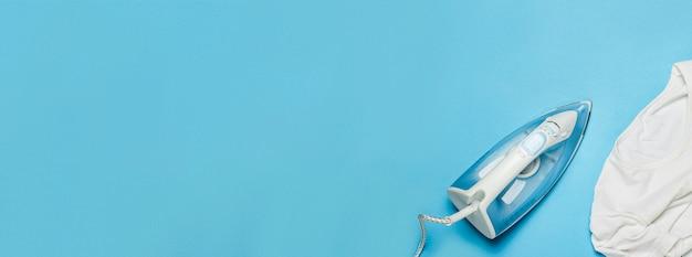 Утюг для глажения вещей и белая футболка на синем фоне.