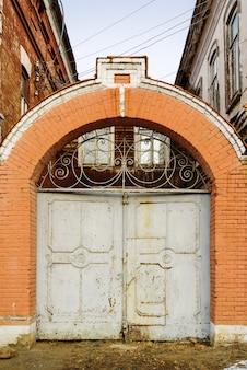 古い建物の中庭へのレンガのアーチのある鉄の門の写真は、ロシアのオレンブルクで撮影されました