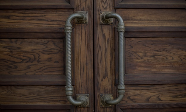 Iron handles on a wooden brown door on the street for design