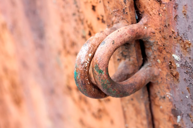 Iron hinges for a padlock on a metal door with old cracked paint and rust