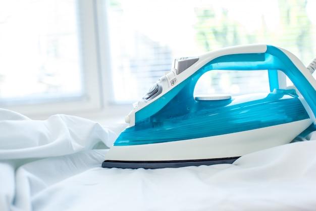 Iron on ironing board on light home interior surface