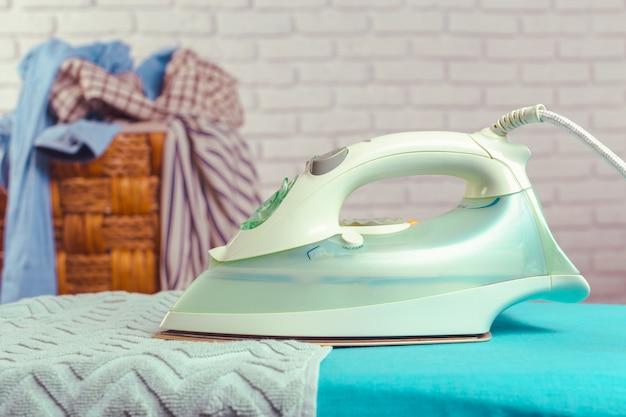 Iron on ironing board on light home interior