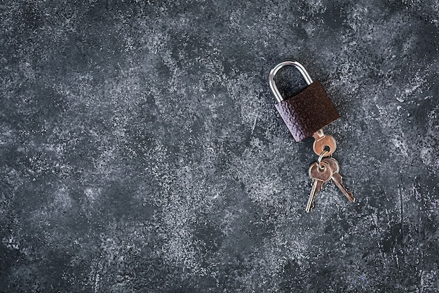 Iron lock with keys on grey background. top view.