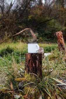 森の中の切り株に鉄製のマグカップが立っています。温かい飲み物から蒸気が発生します。