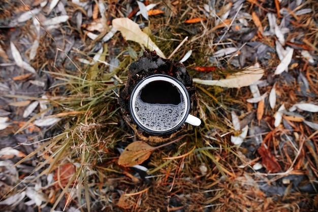 屋外で、温かい飲み物と鉄のマグカップ。上面図、クローズアップ。アウトドアアクティビティのコンセプト