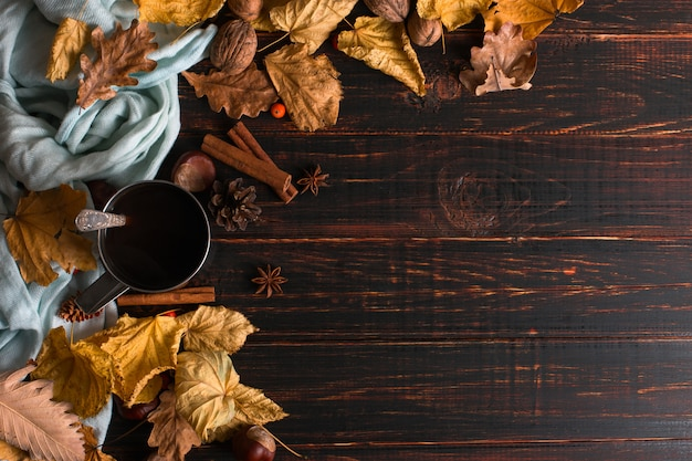 Iron mug with black coffee, spices, on a background of a scarf, dry leaves on a wooden table. autumn mood, a warming drink. copyspace.
