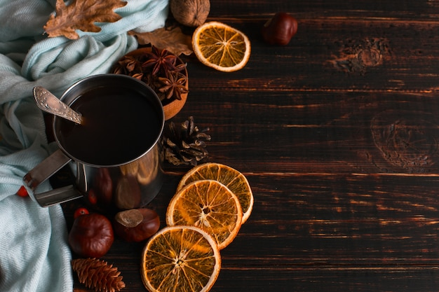 Iron mug with black coffee, spices, dry oranges, on a background of a scarf, dry leaves on a wooden table. autumn mood, a warming drink. copyspace.