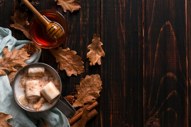 Iron mug with cocoa, honey, marshmallows, spices, on a background of a scarf, dry leaves on a wooden table. autumn mood, a warming drink. copyspace.