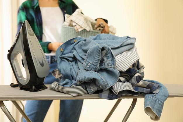 アイロン台と洗濯かごを持つ女性のアイロン