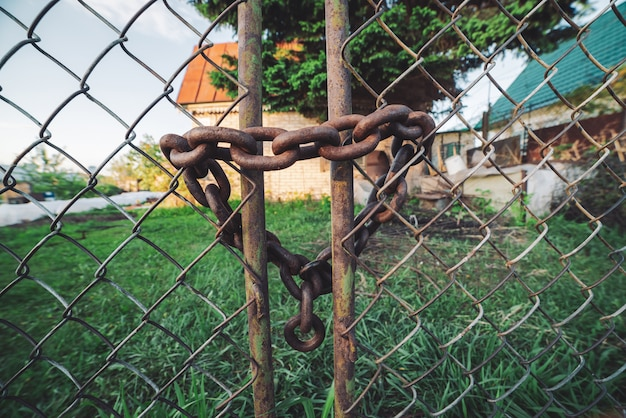 Iron rusty chain-link grid fence.