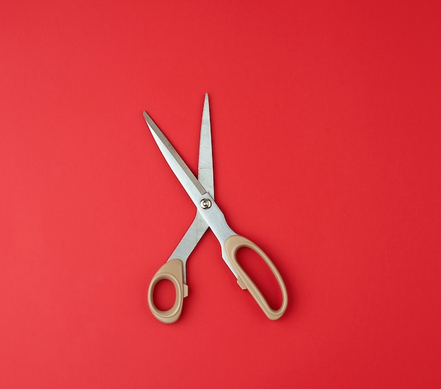 Iron scissors with a beige plastic handle on a red paper