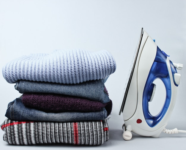 Iron and stack of clothes on gray table