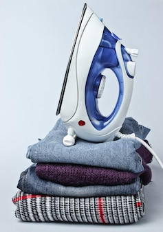 Iron on stack of clothes on gray table