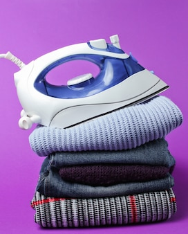 Iron on stack of clothes on purple table