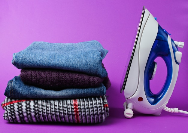Iron and stack of clothes on purple table