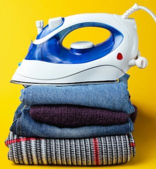 Iron on stack of clothes on yellow table