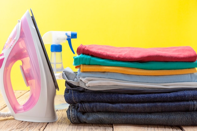 Iron and stack of colored clothes yellow background
