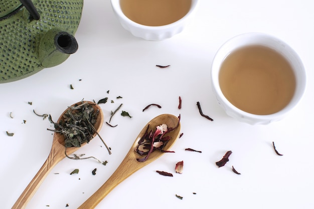 Iron teapot cups wooden spoon tea leaves dried hibiscus white background