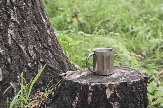 Железная туристическая кружка стоит на пне в лесу
