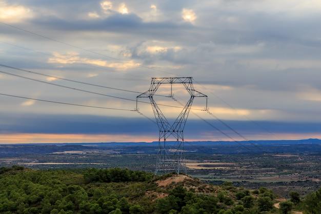 Железная башня электричества на горе с восходом солнца