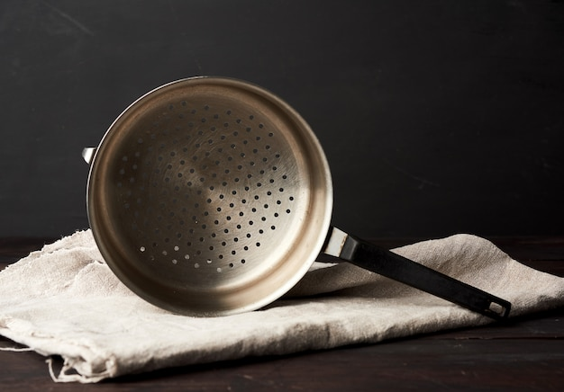 Iron vintage colander on a wooden table