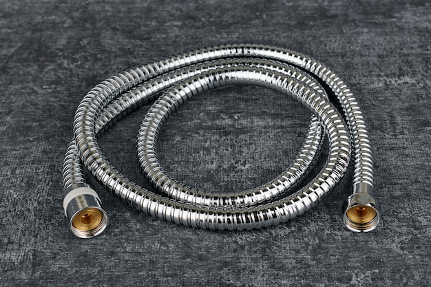 Iron water hose for shower on grey background, close up