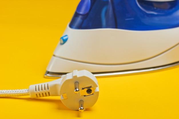 黄色に分離された電気プラグ付きの鉄