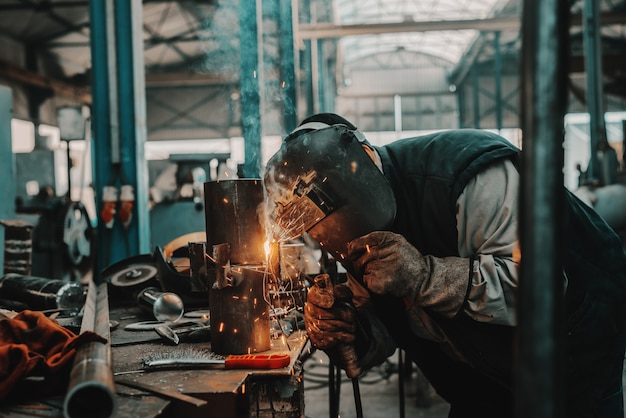 Металлургический рабочий в защитном костюме, маске и перчатках сваривает трубу. интерьер мастерской.
