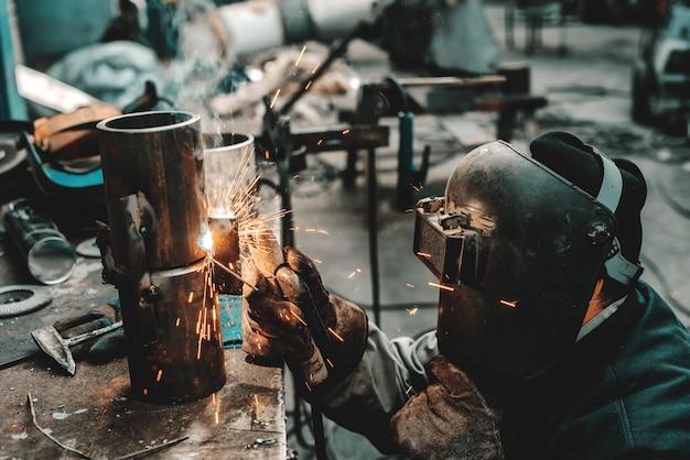 防護服、マスク、手袋の溶接パイプの鉄の労働者。ワークショップのインテリア。