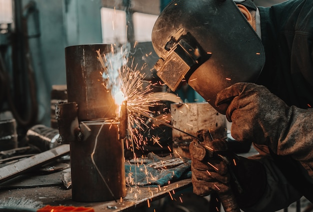 Iron worker in protective suit, mask and gloves welding pipe. workshop interior.