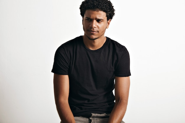 白い壁に黒いノースリーブの綿のtシャツを着てアフロと皮肉な思慮深いハンサムな若い男