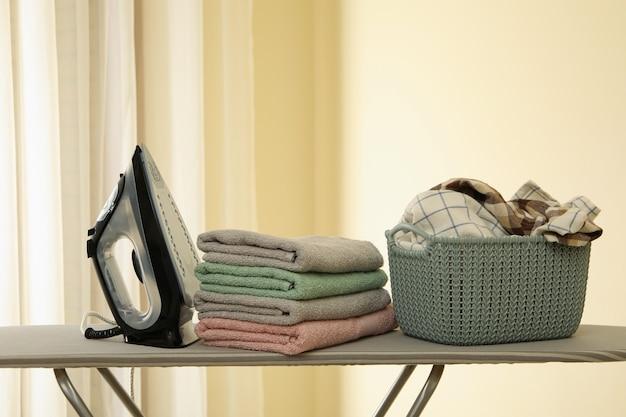 Гладильная доска с утюгом и корзиной полотенец
