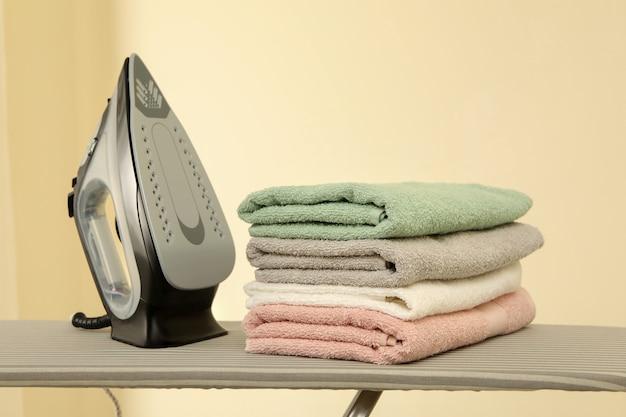 Гладильная доска с утюгом и стопкой полотенец