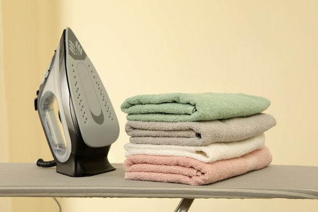Ironing board with iron and pile of towels