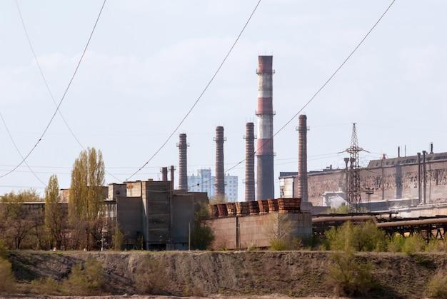 Металлургический завод, расположенный на берегу реки. индустриальный пейзаж.