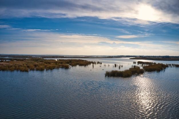 夕方の暖かい明るい光の中でウクライナのドニエプル川のサマラ川にたまらない洪水。空中パノラマドローンショット