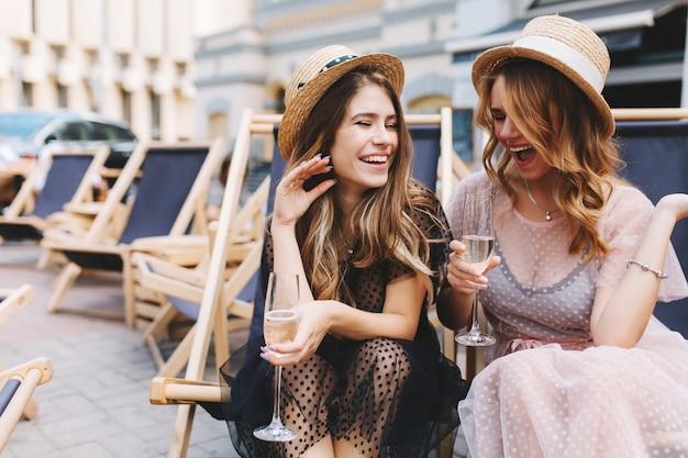 Неотразимая смеющаяся девушка слушает шутку друга и пьет шампанское