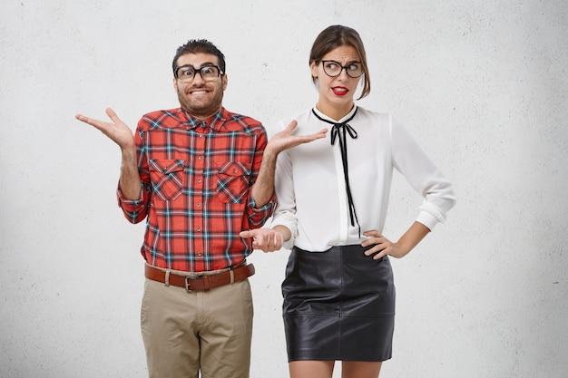 厚いレンズの肩をすくめる、四角い眼鏡をかけた不屈の男性、ためらいがあり、イライラした女性が彼を見ている