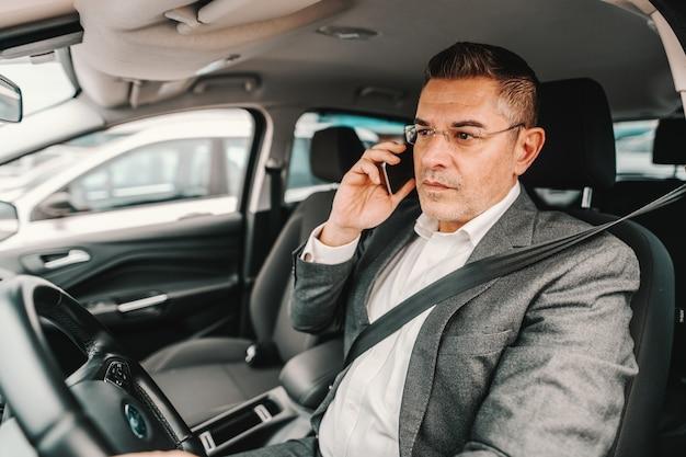 무책임한 중간 나이 든 남자가 차를 운전하고 전화를 위해 스마트 폰을 사용합니다.