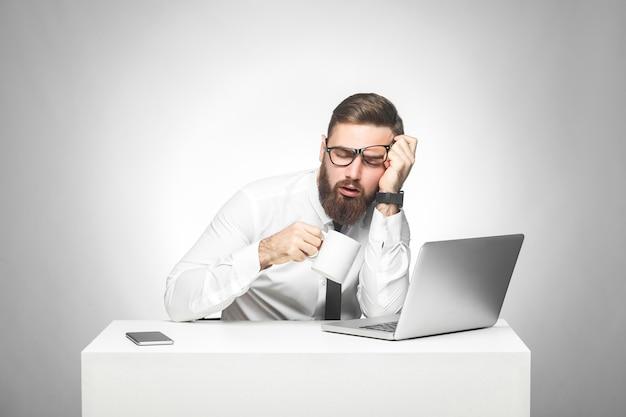 白いシャツと黒いネクタイを着た無責任な疲れた若いマネージャーがオフィスに座って、仕事で眠らないようにしようとしています。コーヒーを飲み、頭を手で持っています。スタジオショット、隔離、屋内