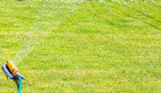 Irrigation system lawn sprinkler spray water over fresh grass in garden