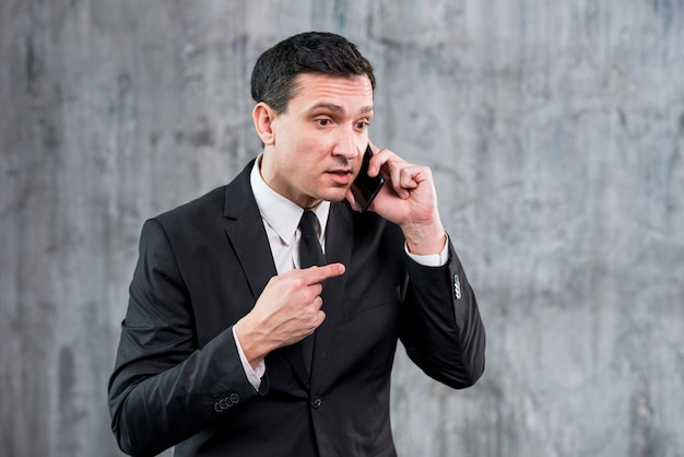 Irritated adult businessman speaking on phone
