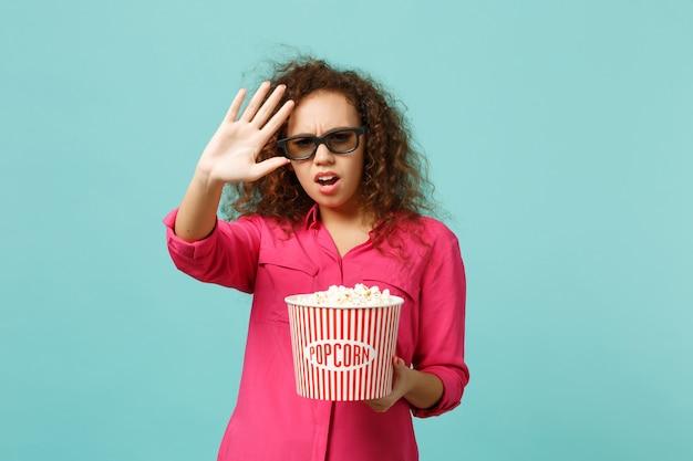 3d 아이맥스 안경을 쓴 화난 아프리카 소녀가 파란색 청록색 배경에 격리된 정지 제스처를 보여주는 팝콘을 들고 영화를 보고 있습니다. 영화, 라이프 스타일 개념에서 사람들의 감정. 복사 공간을 비웃습니다.
