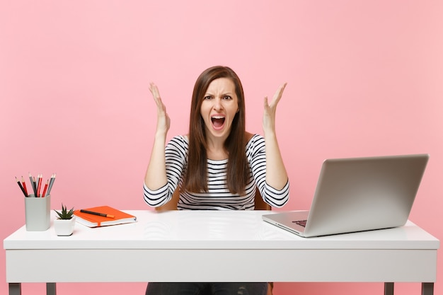 Irritated angry woman in casual clothes screaming spreading hand sit work at white desk with contemporary pc laptop isolated on pastel pink background. achievement business career concept. copy space.