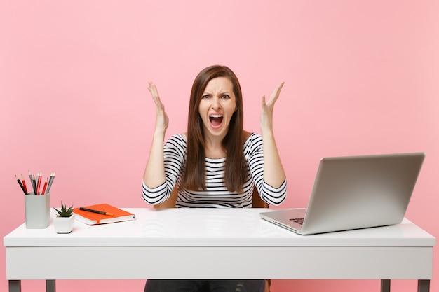 Раздраженная злая женщина в повседневной одежде кричит, раскинув руки, сидит за белым столом с современным ноутбуком