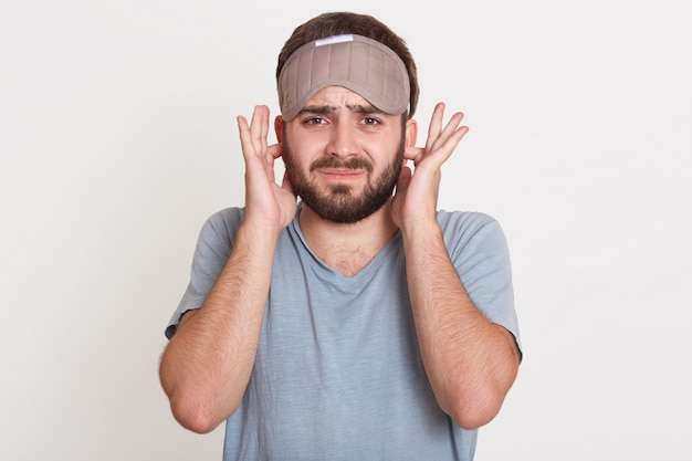 Irritated angry young man having beard, looking directly  covering his ears with fingers, wearing t shirt and sleeping mask