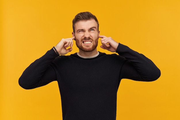 Irritated angry young man with beard in black longsleeve looks annoyed and closed ears by fingers standing over yellow wall