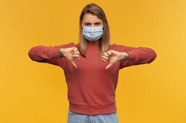 노란색 벽 위에 절연 양손으로 아래로 엄지 손가락을 보여주는 코로나 바이러스에 대한 얼굴에 바이러스 보호 마스크에 짜증이 난 젊은 여성